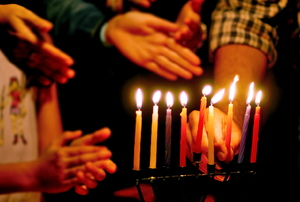 A menorah with lit candles and people's hands around it.