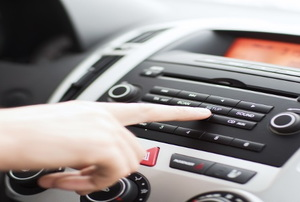 A woman presses a button on a car radio