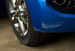 Scuffed front bumper on a blue car