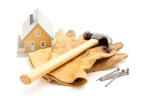 A small model of a house next to a hammer, pair of work gloves, and nails.