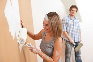 A woman painting a wall white.