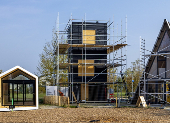 three different tiny homes under construction