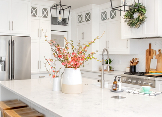 light, open farmhouse kitchen with sink island featuring pink flowers in vases