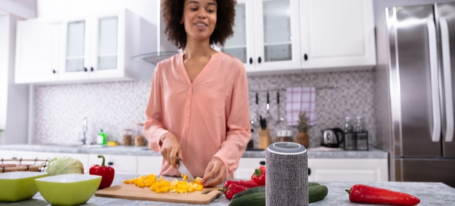 woman cutting peppers in a kitchen with a smart speaker