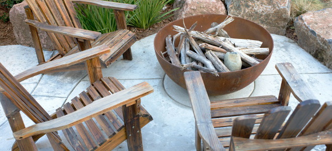 an unlit firepit surrounded by chairs