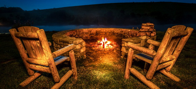 a burning fire pit by a lake surrounded by a stone wall and wooden chairs