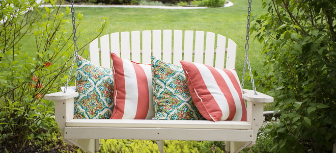 A porch swing with decorative pillows.