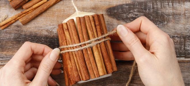 Cinnamon sticks around a candle.