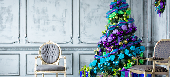 Colorful ombre Christmas tree and presents in a grey room