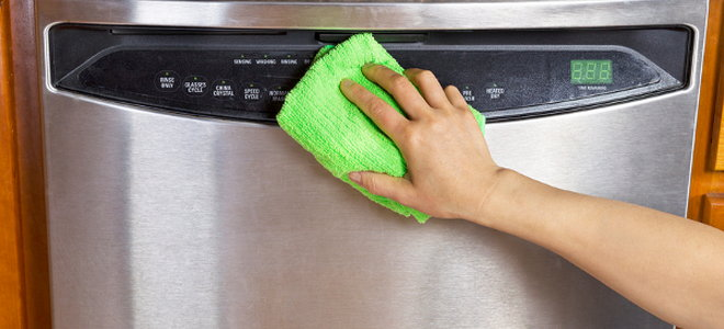 Someone cleaning a stainless steel dishwasher with a green cloth.