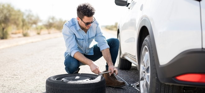 a man cranking a car jack to change his tire