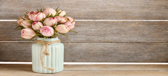 A painted DIY vase with pink flowers in it for Valentine's Day.