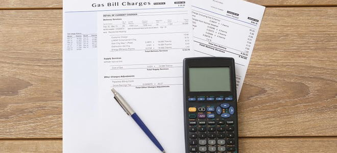 A collection of gas bills with a calculator and pen on a desk.