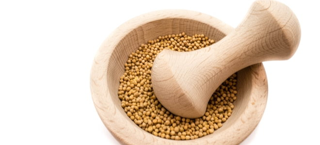 mustard seeds in a mortar with pestle