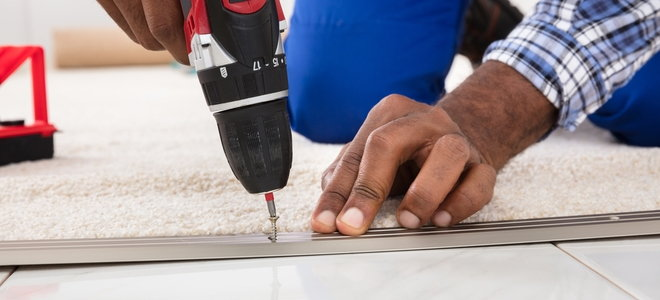 hands drilling in the edge of the carpet