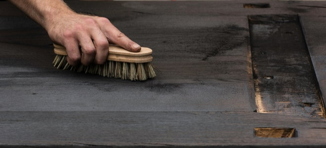 hand brushes a charred piece of wood