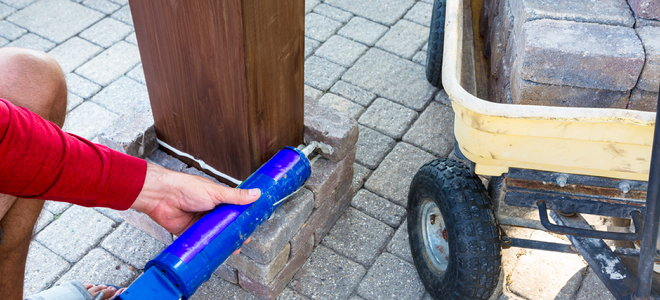 gluing bricks to support a wooden post