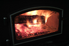 a fire burning inside a fireplace with a clear door.