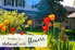 A flowerbed with a house in the background and the words