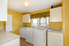 a room with yellow walls and white washer, dryer, and cabinets