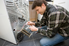man repairing a dryer