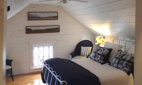 """Nantucket cottage"" bedroom with wrought iron, queen bed, AC/heat and white washed walls.  It says...Cape Cod!"