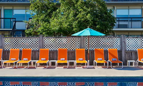 Pool with colorful lounge chairs and umbrellas