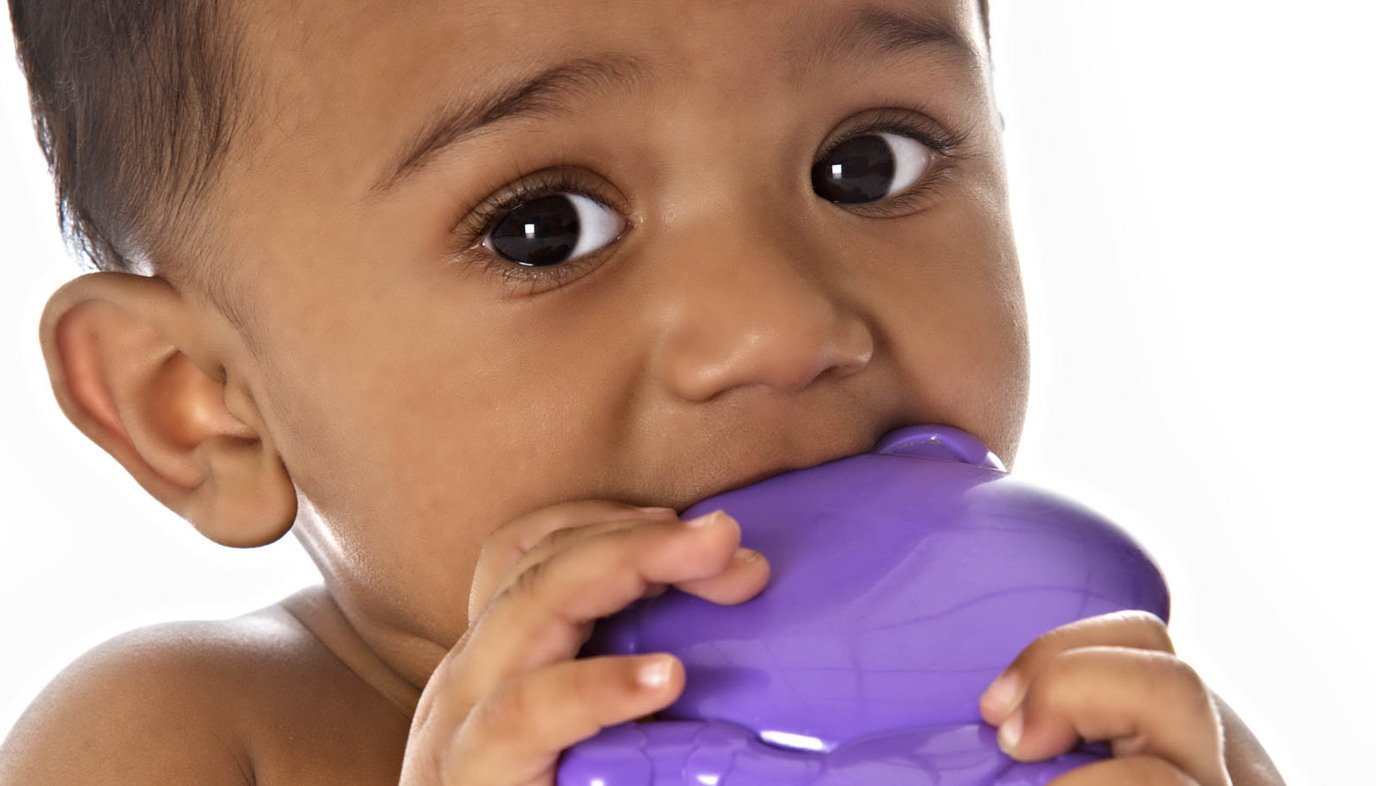 baby chewing on purple toy