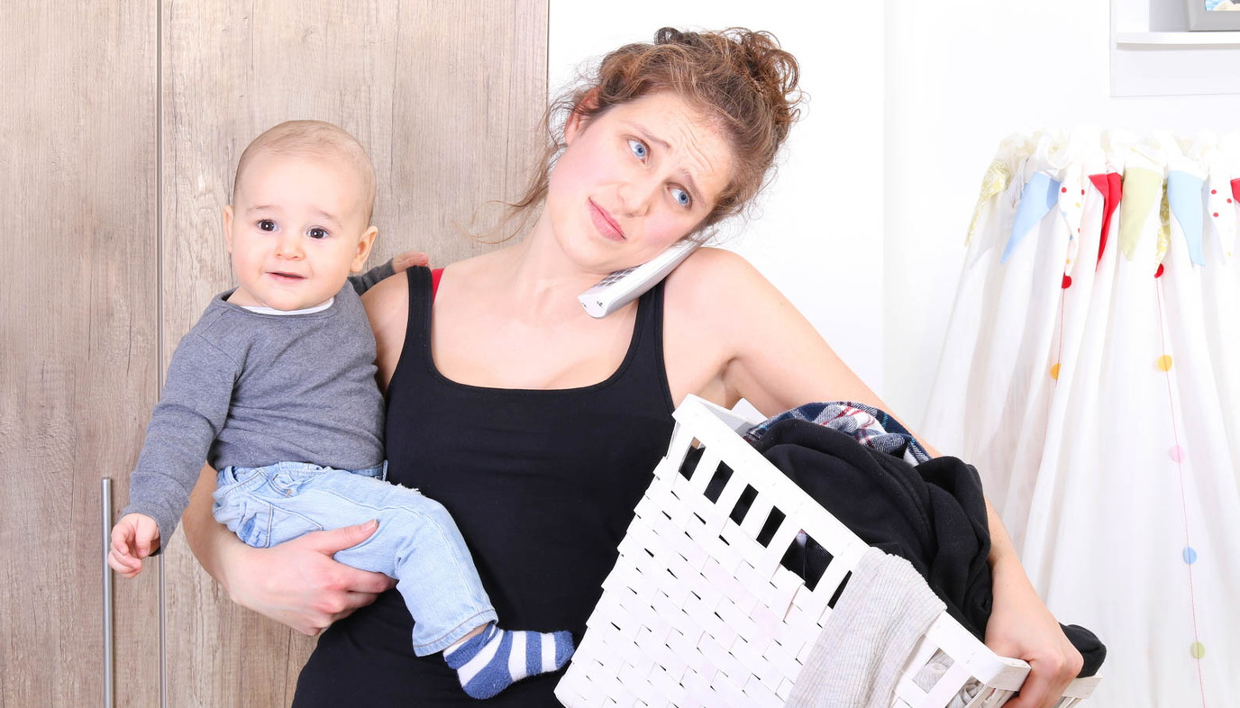 parent with child new mom exhaustion on phone doing laundry