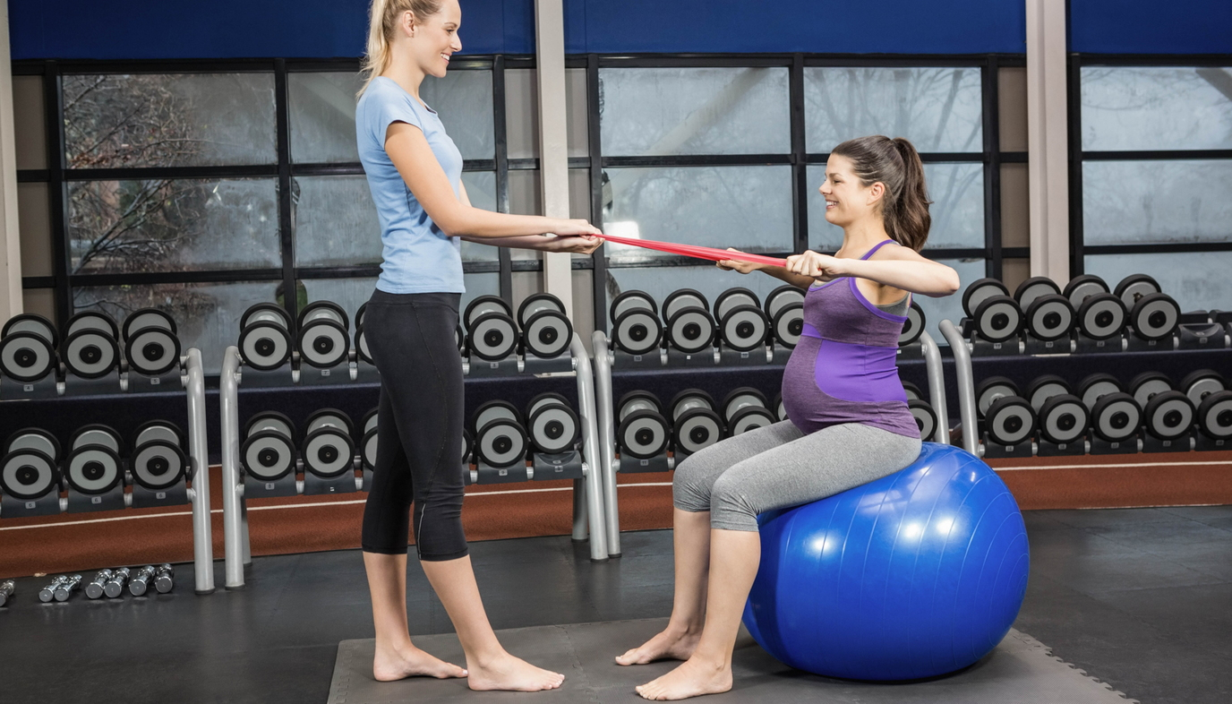 pregnant woman exercising with trainer