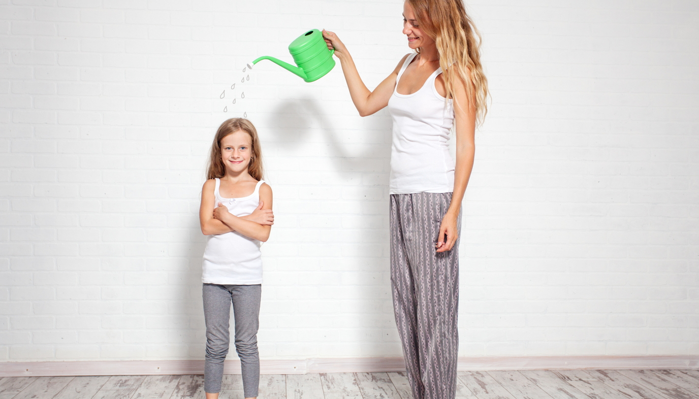 mom with watering can over daughter