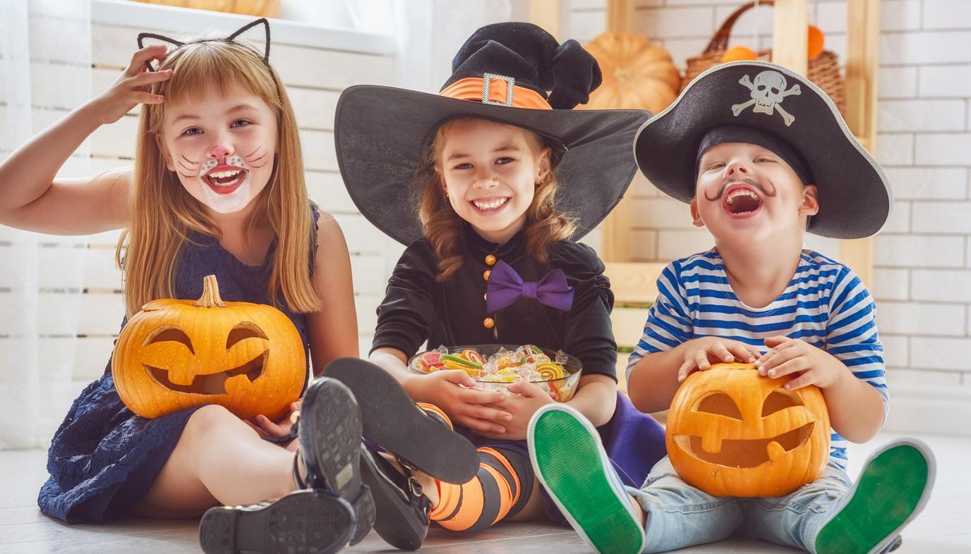children in Halloween costumes holding pumpkins