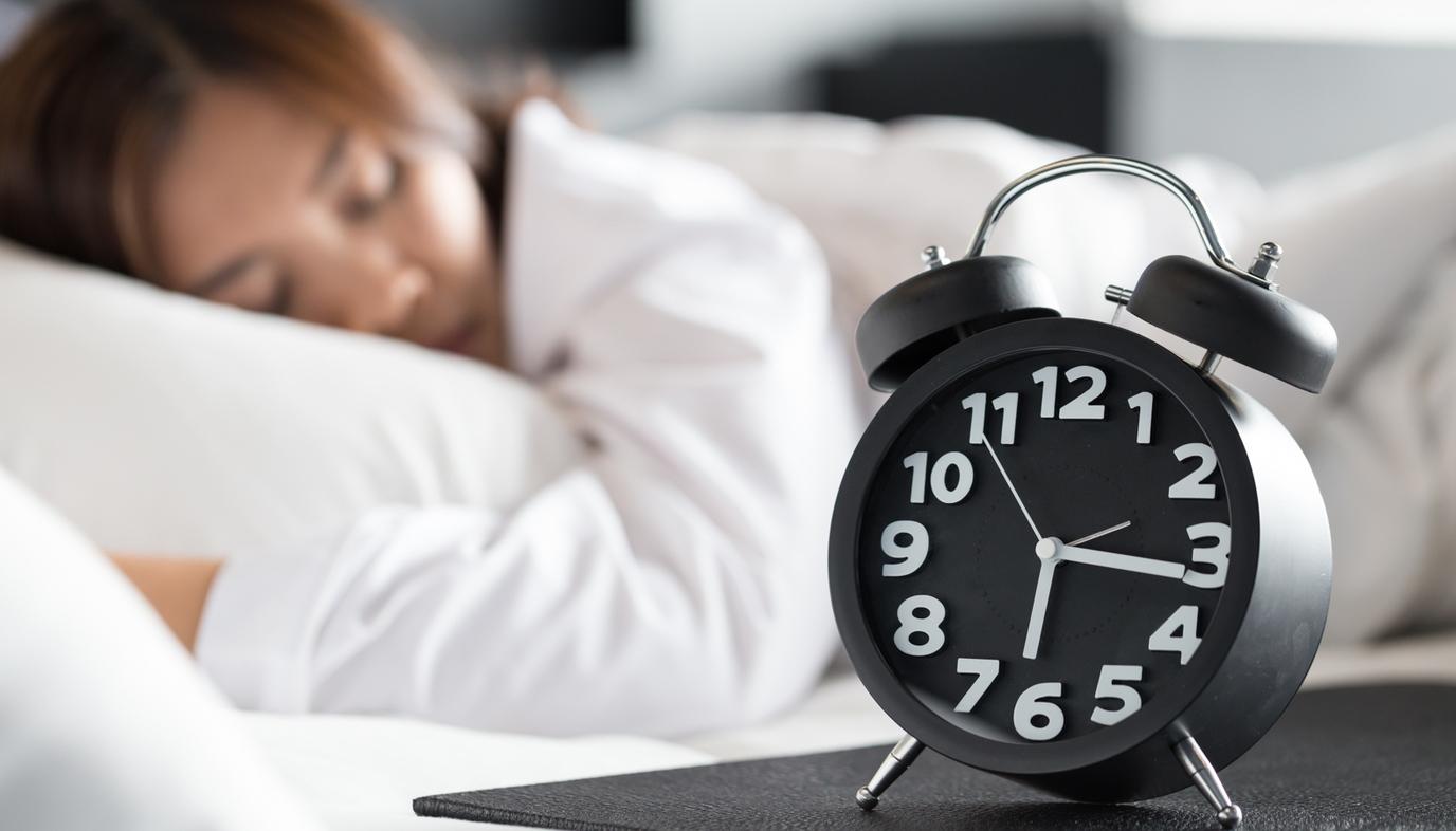 woman sleeping next to alarm clock