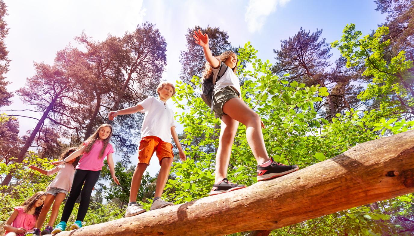 kids at summer camp walking over big log