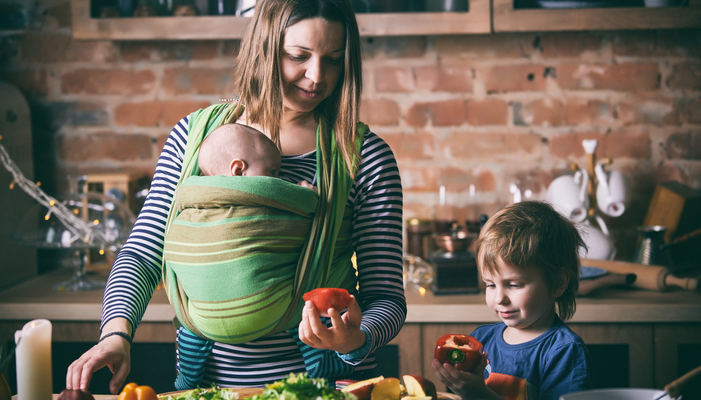 mom carrying baby in baby wrap while  preparing fruit with daughter
