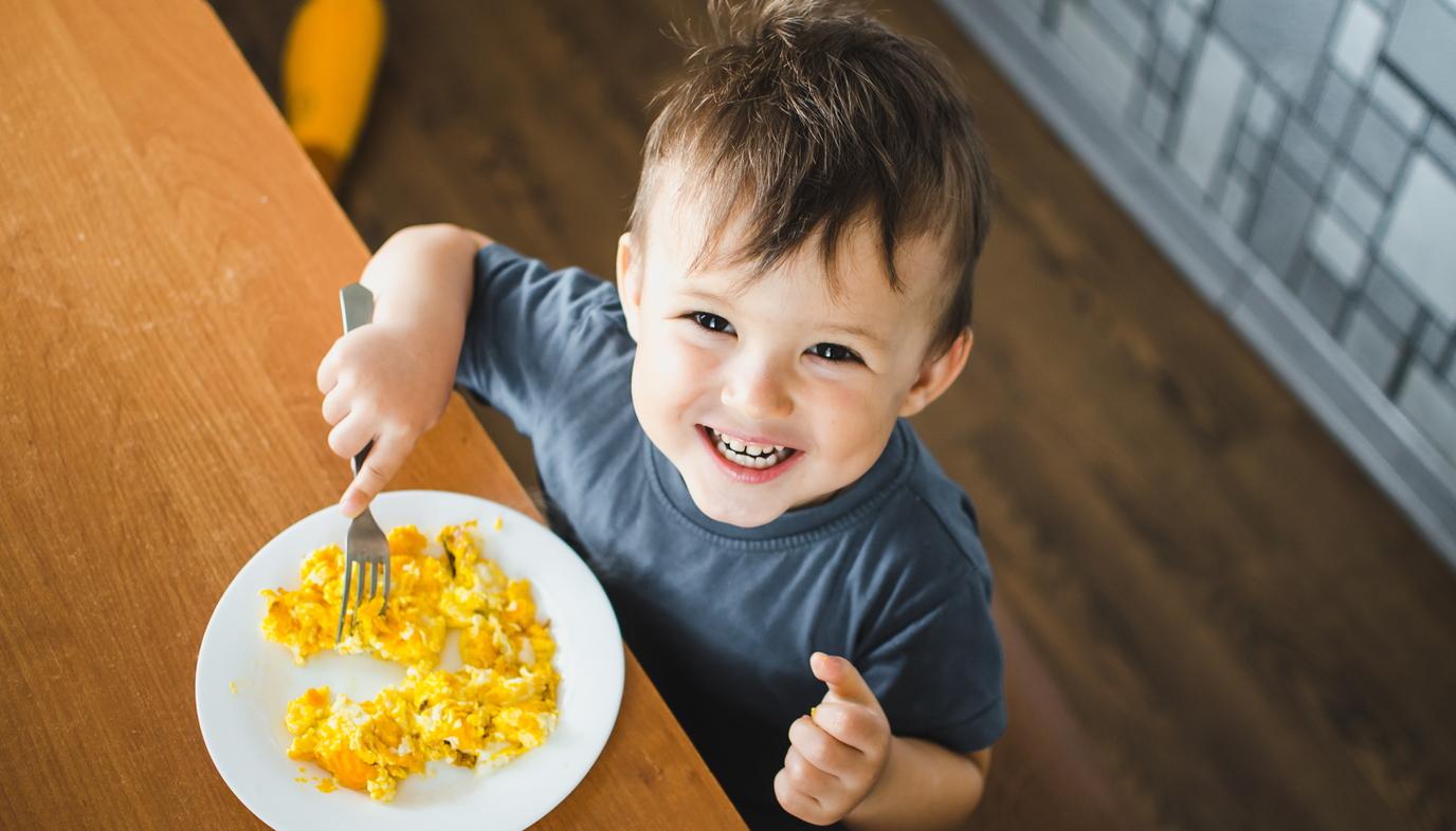 little boy eating scrambled eggs