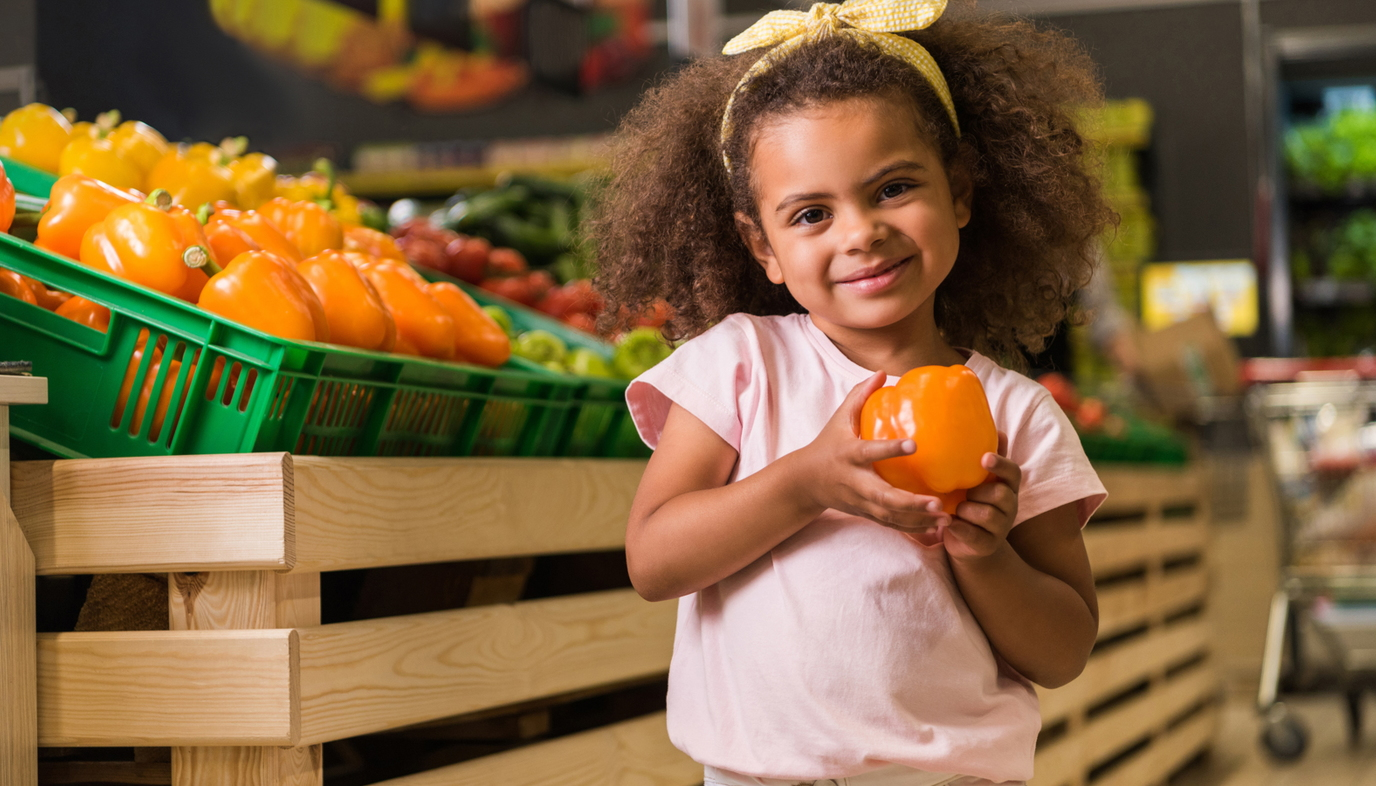 girl selecting vegetable from the grocery store