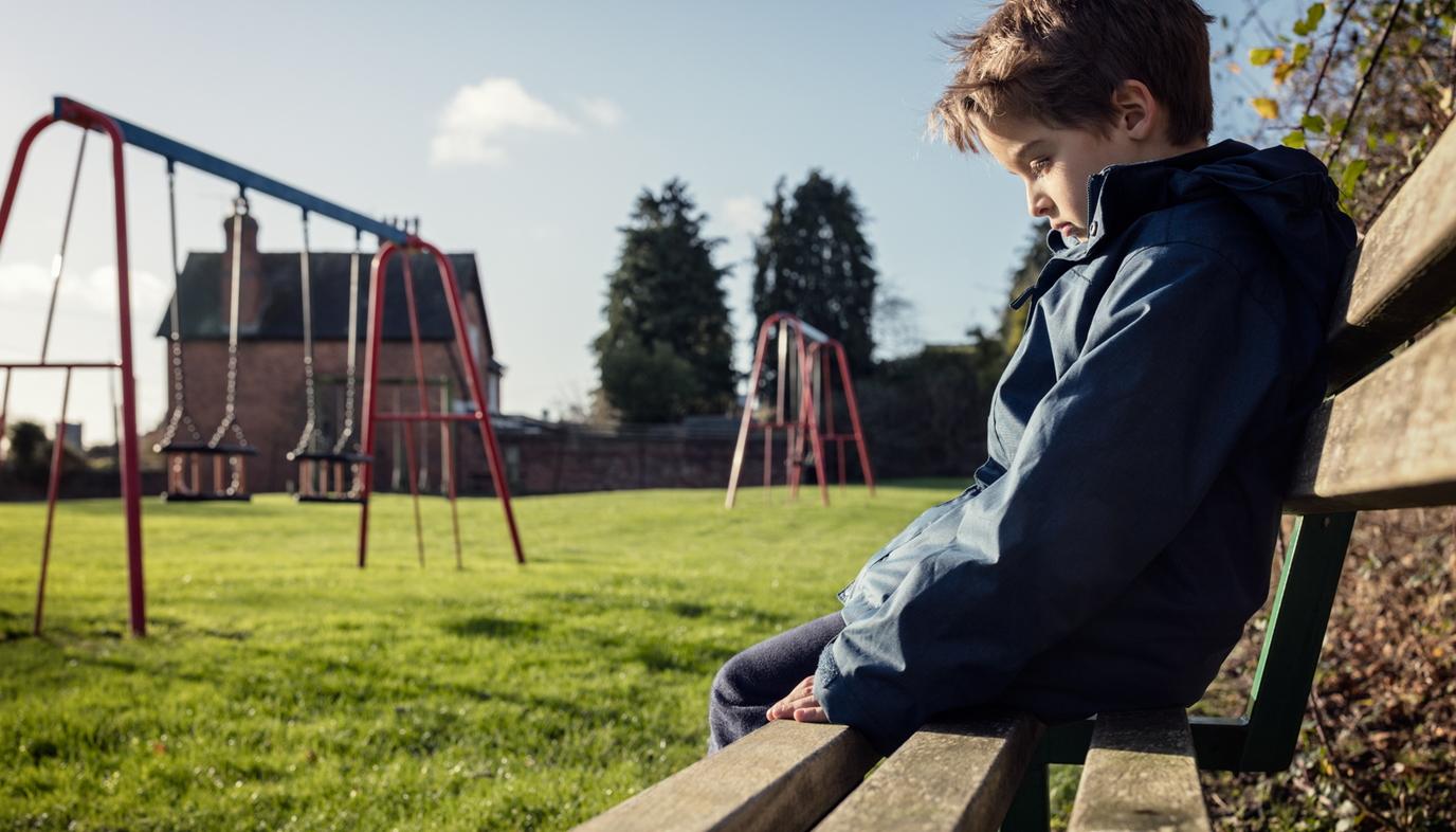 sad boy sitting alone at a park