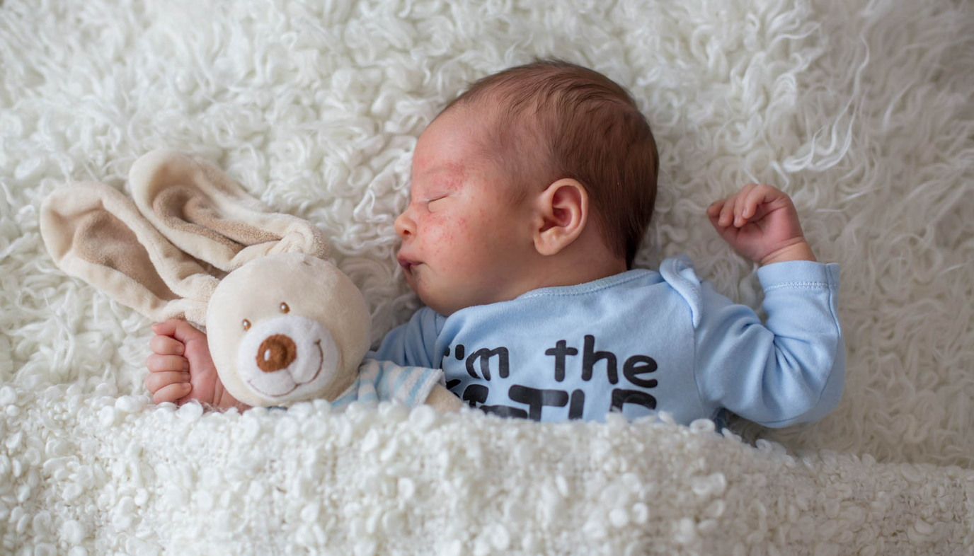 sleeping baby inside white blanket with teddy bear