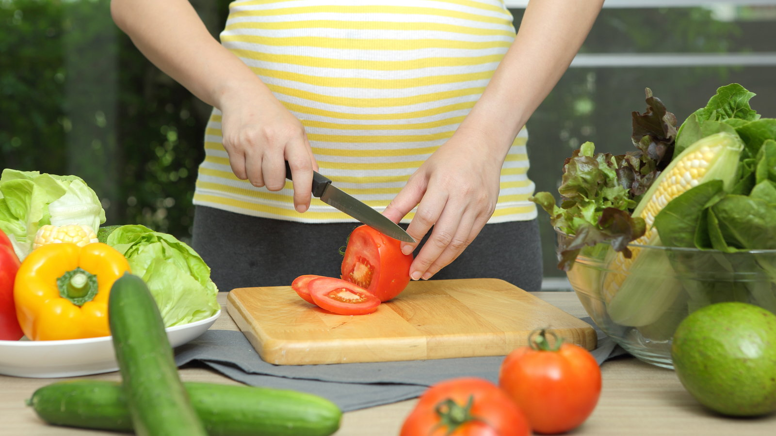 pregnant mom cutting up vegetables