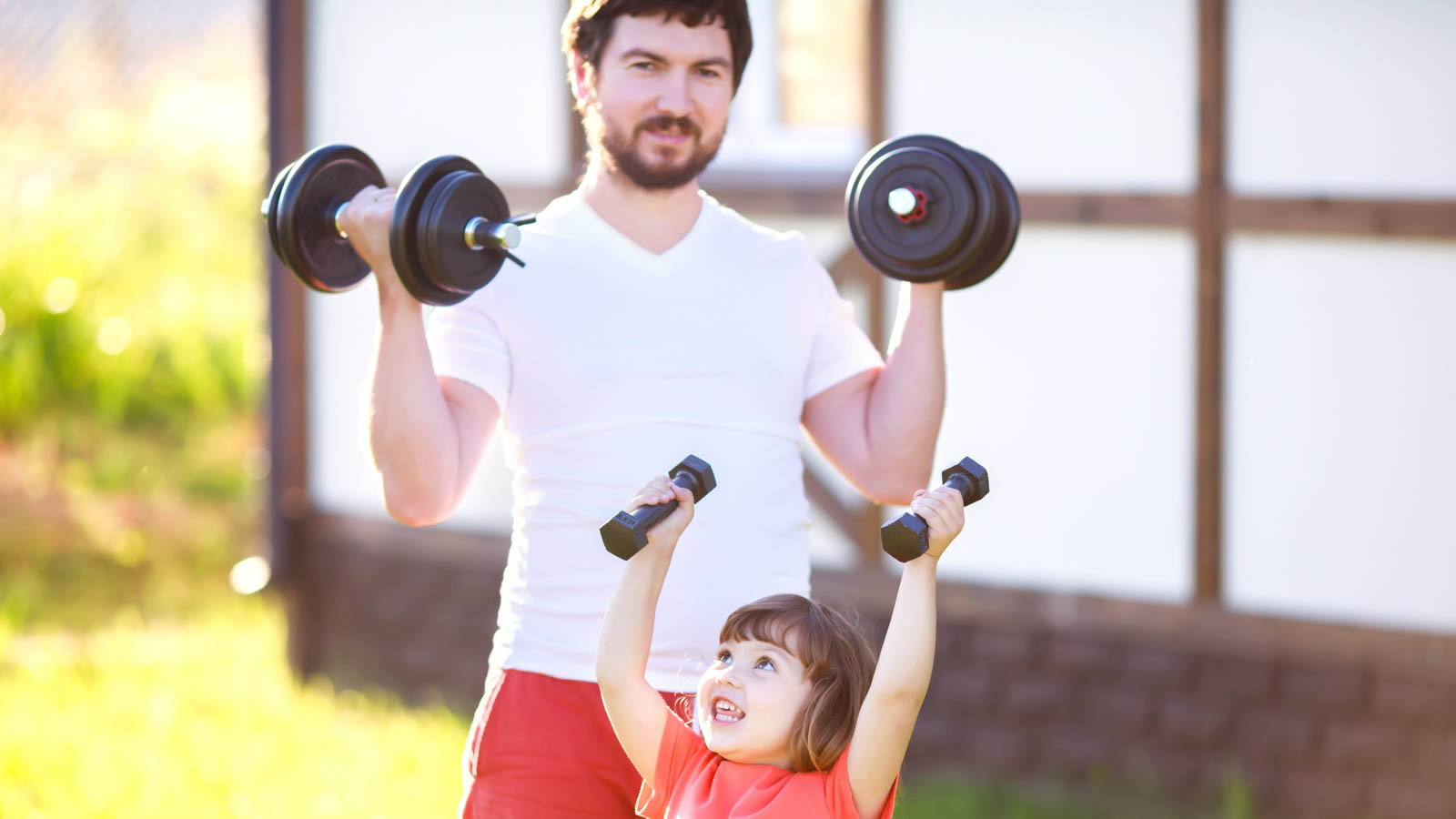 dad lifting weights with daughter