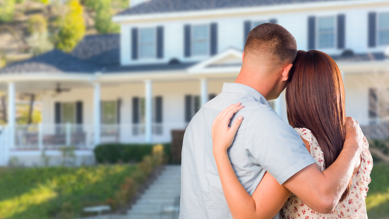 couple embracing in front of house