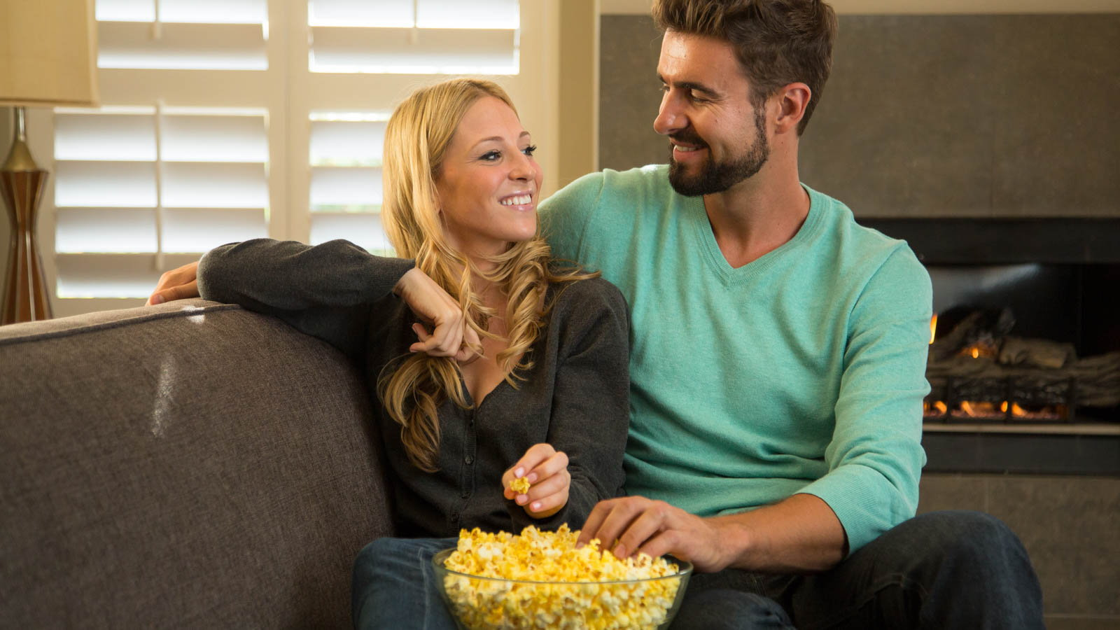 couple eating popcorn on the couch