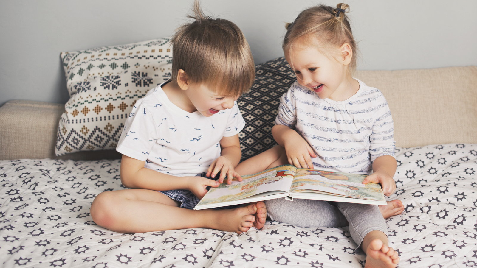 toddlers reading a book together