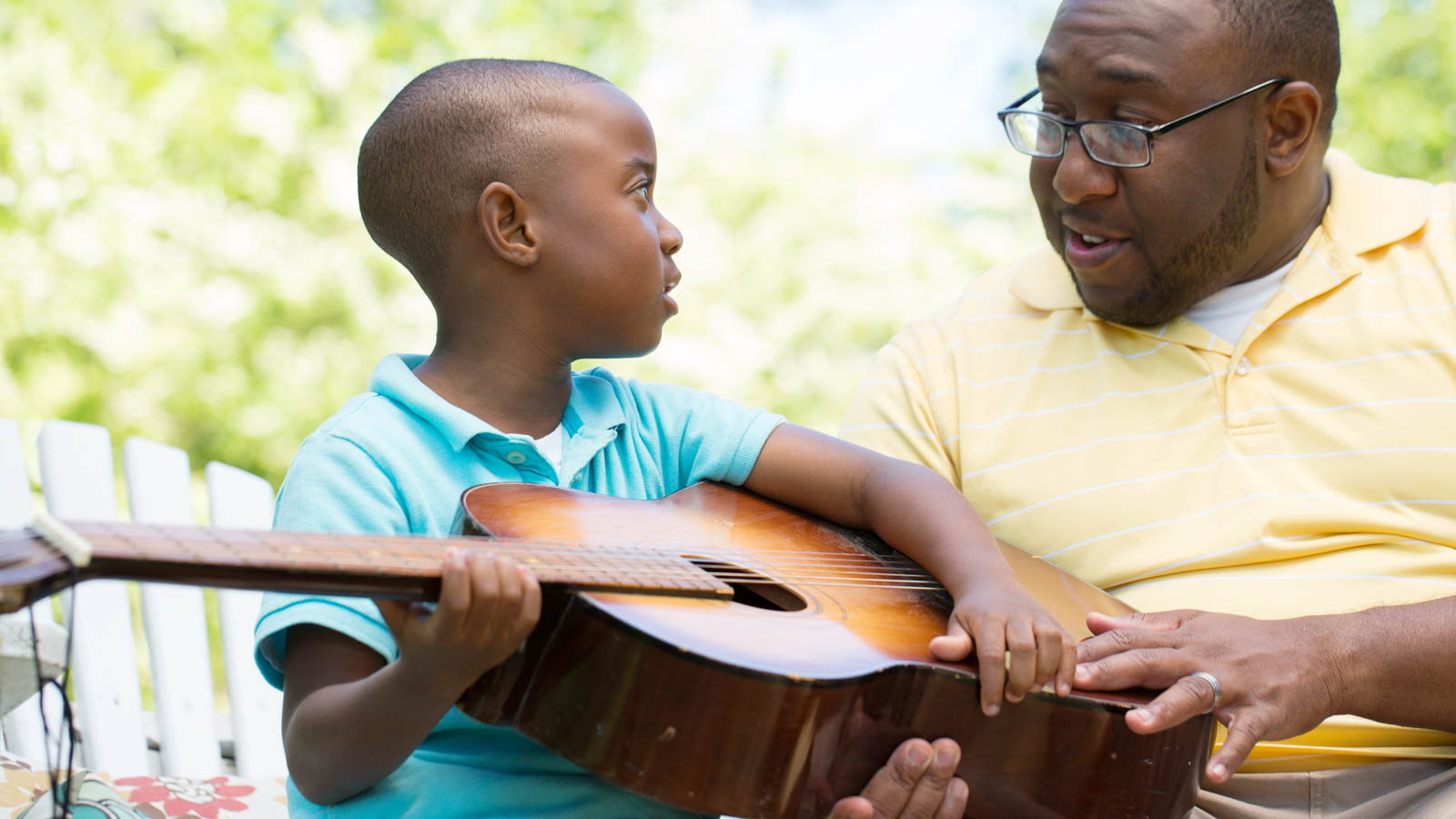 father showing son how to play the guitar
