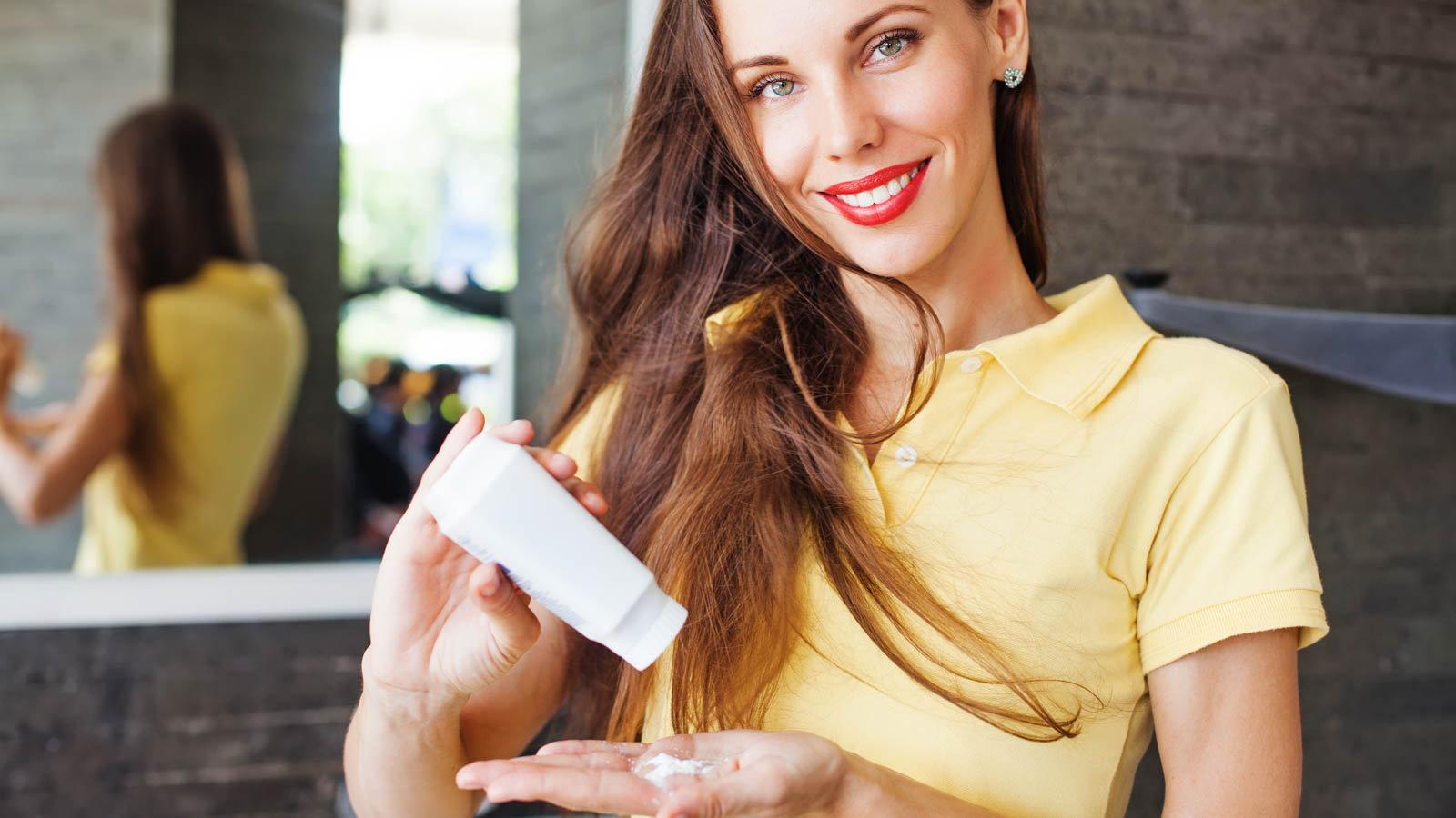 woman with beautiful hair using dry shampoo