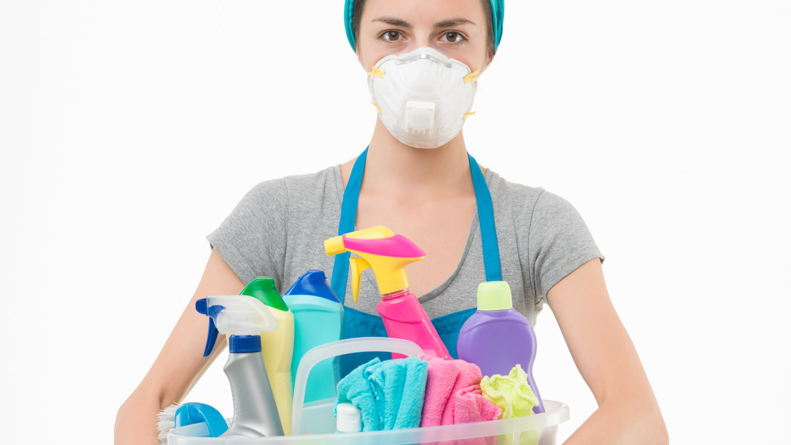 woman wearing mask while holding basket of cleaning supplies