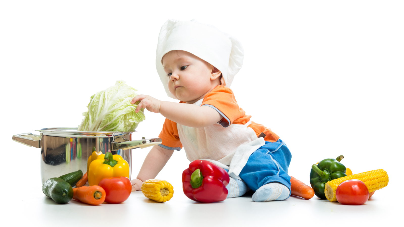 baby wearing chef's hat putting vegetables in pot