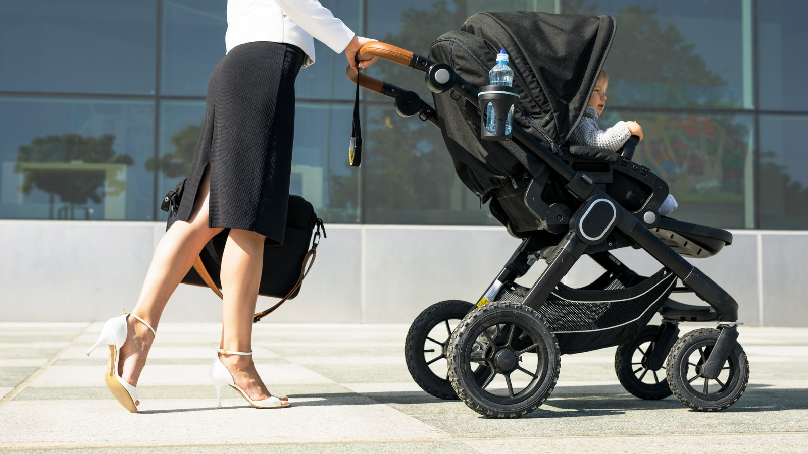 career mom pushing baby stroller