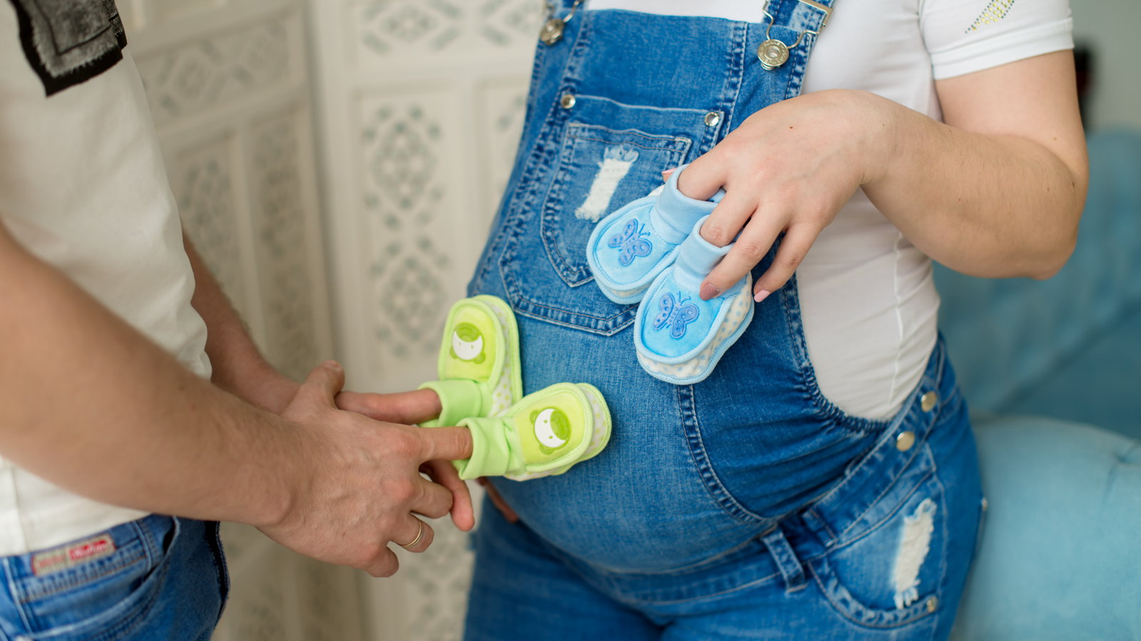 pregnant woman with husband holding 2 sets of baby shoes